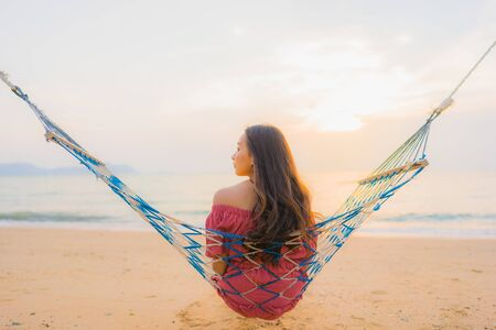 Portrait beautiful young asian woman sitting on the hammock with smile happy neary beach sea and ocean for leisure travel and vacation at sunset time Фото со стока - 131351130