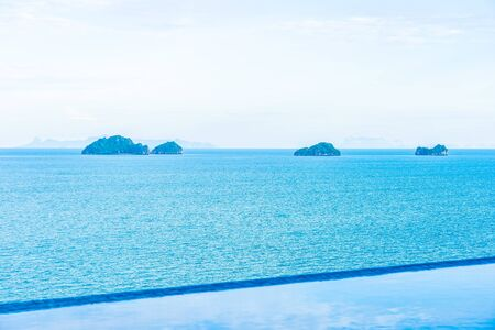 Beautiful outdoor swimming pool with sea ocean on white cloud blue sky for holiday vacation travel concept