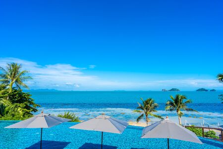 Beautiful luxury outdoor swimming pool in hotel resort with sea ocean around coconut palm tree and white cloud on blue sky for holiday vacation travel