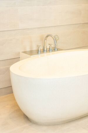 Beautiful luxury elegance white bathtub and water faucet decoration in bathroom interior 스톡 콘텐츠