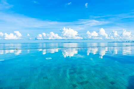 Beautiful outdoor swimming pool in hotel resort nearly sea ocean beach on white cloud blue sky for leisure relax and holiday vacation