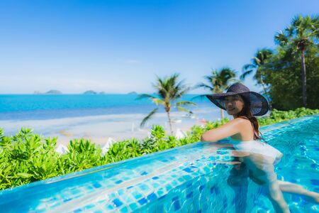 Portrait beautiful young asian woman relax in luxury outdoor swimming pool in hotel resort nearly beach sea ocean for holiday vacation concept