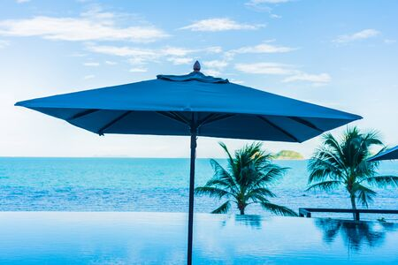 Umbrella and chair around beautiful luxury outdoor swimming pool with sea ocean view in hotel resort for holiday vacation travel concept