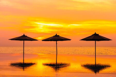 Umbrella and chair around swimming pool neary sea ocean beach at sunrise or sunset time for leisure travel and vacation Stock Photo
