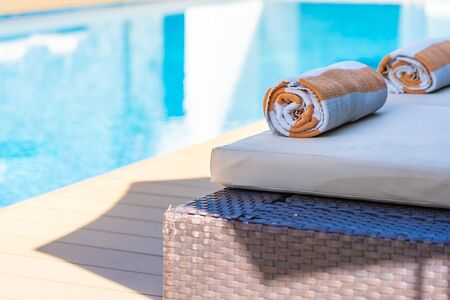 Towel on bed around swimming pool in hotel resort for relax Stock Photo