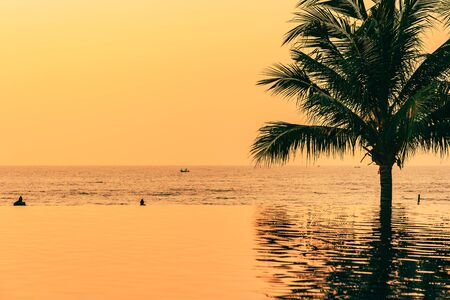 Beautiful landscape outdoor with coconut palm tree around swimming pool in hotel and resort at sunrise or sunset time for leisure vacation and travel