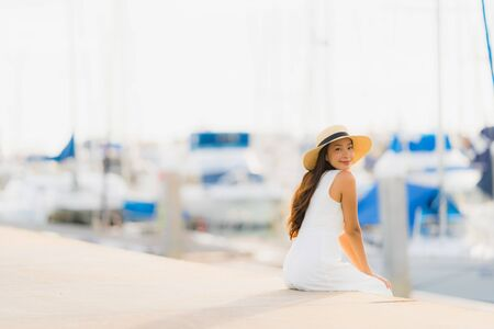 Portrait beautiful young asian woman leisure smile happy relax around yacht port at sea ocean for holiday vacation concept