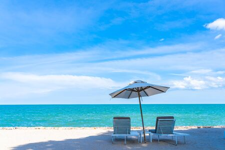 Beautiful umbrella and chair around beach sea ocean with blue sky for travel vacation Stock Photo