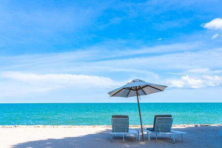 Schöner Regenschirm und Stuhl um Strand Meer Ozean mit blauem Himmel für Reiseurlaub Standard-Bild