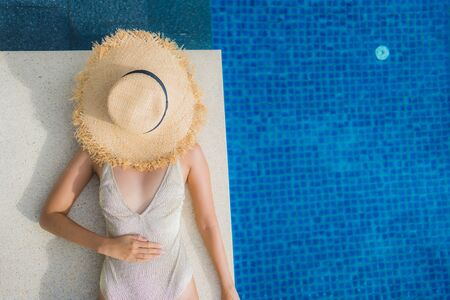 Portrait young asian woman relax smile happy around swimming pool in hotel and resort for holiday vacation travel concept Stok Fotoğraf