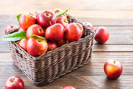 Una gran cantidad de fruta de manzana roja en la canasta marrón en la mesa