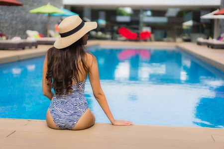 Beautiful portrait asian woman relax happy smile around outdoor swimming pool in holiday vacation