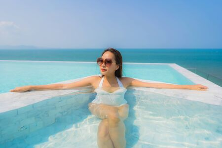 Portrait beautiful young asian woman happy smile relax in swimming pool with sea ocean and blue sky for travel vacation and leisure Reklamní fotografie - 132071497