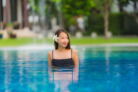 Portrait young asian woman relax smile happy around outdoor swimming pool in hotel resort with sea ocean view in holiday vacation concept Reklamní fotografie - 132071517