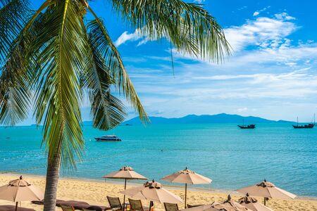 Schönes tropisches Strandmeer und Ozean mit Kokospalme und Regenschirm und Stuhl auf blauem Himmel und weißer Wolke für Urlaubsreisen Standard-Bild