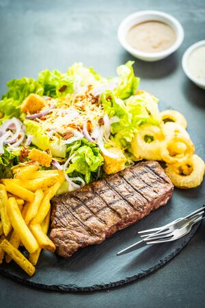 Grilled beef meat steak with french fries onion ring with sauce and fresh vegetable in black slate
