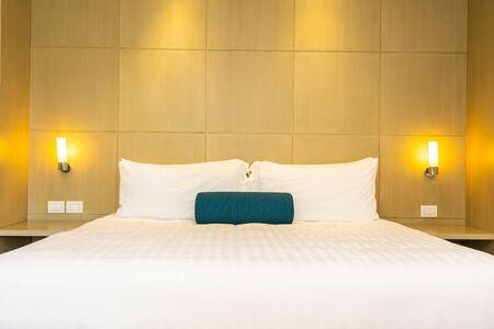 Schönes weißes Kissen und Decke auf dem Bettdekorationsinnenraum des Schlafzimmers Standard-Bild