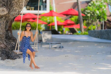 Portrait young asian woman sitting on swing rope and sea around beach sea ocean coconut palm tree for travel in holiday vacation concept
