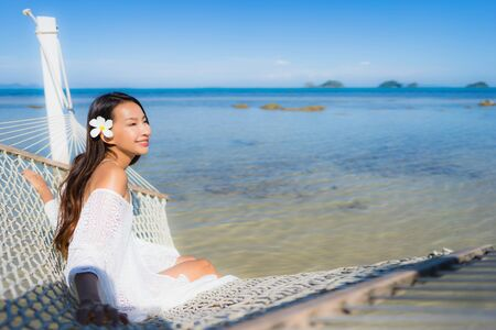 Portrait beautiful young asian woman sitting on hammock around sea beach ocean for relax in holiday vacation travel concept 版權商用圖片