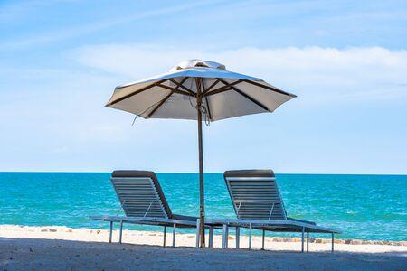 Schöner Regenschirm und Stuhl um Strand Meer Ozean mit blauem Himmel für Reiseurlaub