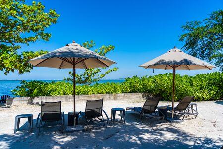 Sonnenschirm und Stuhl am Strand und Meer mit blauem Himmel für den Urlaub Standard-Bild