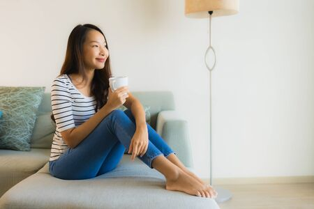 Portrait beautiful young asian woman on sofa with coffee cup and relax