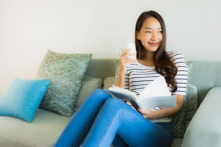 Portrait beautiful young asian women reading book with coffee cup on sofa in living room