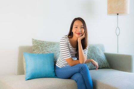 Portrait beautiful young asian woman smile happy on sofa in living room interior area