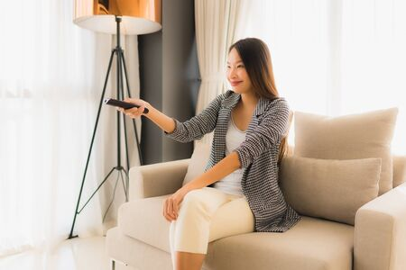 Portrait beautiful young asian women change channel tv in living room interior