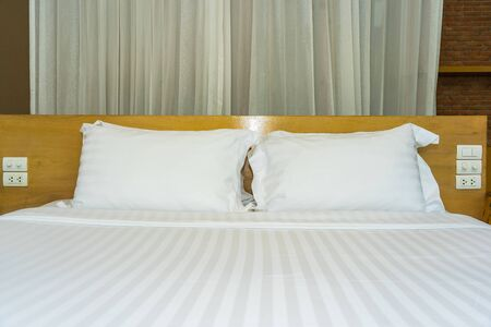 Pillow and blanket on bed with light lamp decoration interior of bedroom
