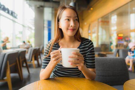 Retrato de hermosas mujeres asiáticas jóvenes en cafetería cafetería y restaurante mediante teléfono móvil