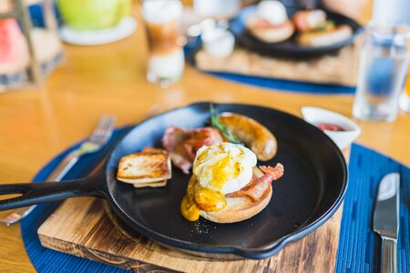 Breakfast set with egg benedict sausage in hot pan on wooden table