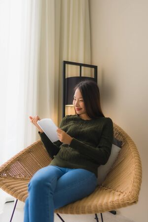 Portrait beautiful young asian women reading book and sitting on sofa chair in living room area Фото со стока