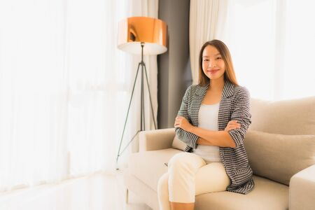 Portrait beautiful young asian women happy smile relax sitting on sofa chair in living room interior