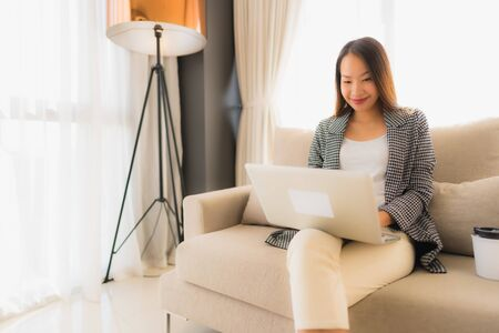 Beautiful young asian portrait using computer and laptop with coffee cup sitting on sofa chair in living room interior Фото со стока