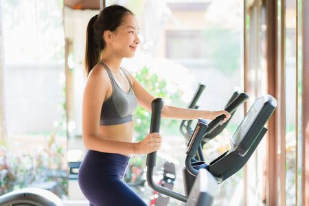 Portrait beautiful young asian woman exercise with fitness equipment in gym interior for good healthy