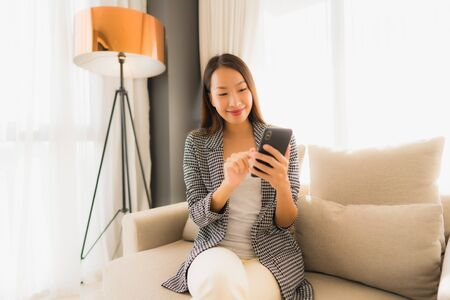 Portrait beautiful young asian women using talking mobile phone and sitting on sofa chair in living room area
