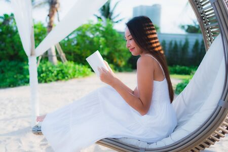 Portrait beautiful asian woman reading book around beach sea ocean in holiday vacation Фото со стока