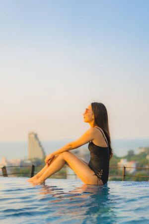 Portrait beautiful young asian women happy smile relax outdoor swimming pool in hotel resort in vacation at sunset time