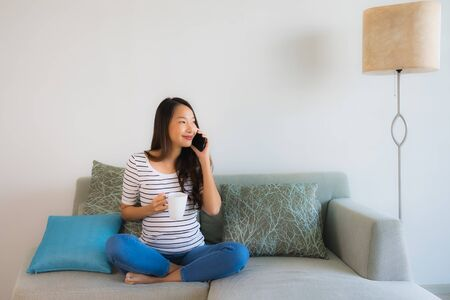 Portrait beautiful young asian woman using or talking mobile phone on sofa living room interior Фото со стока