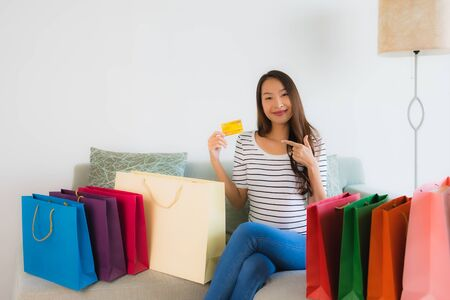 Portrait beautiful young asian women with credit card mobile phone or computer for online shopping on sofa in living room interior Фото со стока