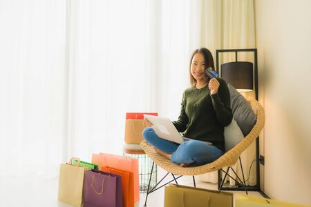Portrait beautiful young asian women sitting on sofa chair using computer laptop or smart and mobile phone with credit card for online shopping Banco de Imagens - 135531383