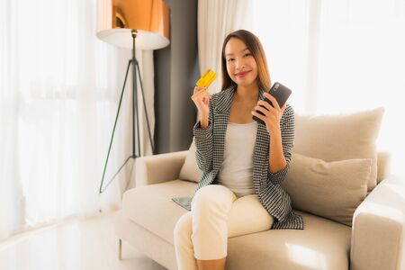 Portrait beautiful young asian women sitting on sofa chair using computer laptop or smart and mobile phone with credit card for online shopping Banco de Imagens - 135531387