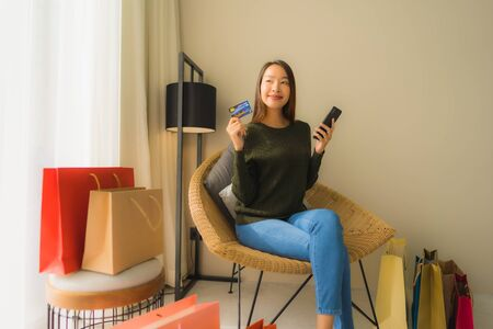 Portrait beautiful young asian women sitting on sofa chair using computer laptop or smart and mobile phone with credit card for online shopping Banco de Imagens - 135531438