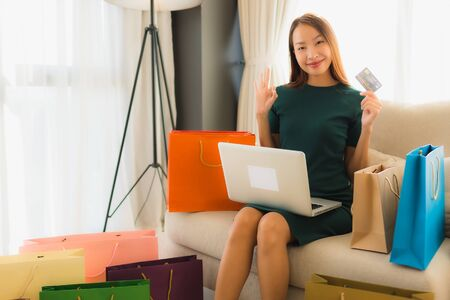 Portrait beautiful young asian women sitting on sofa chair using computer laptop or smart and mobile phone with credit card for online shopping Banco de Imagens - 135531483