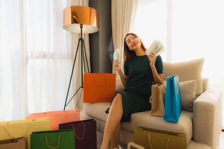 Portrait beautiful young asian women sitting on sofa chair using computer laptop or smart and mobile phone with credit card for online shopping Banco de Imagens - 135531644