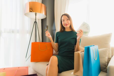 Portrait beautiful young asian women sitting on sofa chair using computer laptop or smart and mobile phone with credit card for online shopping