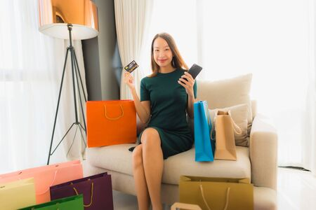 Portrait beautiful young asian women sitting on sofa chair using computer laptop or smart and mobile phone with credit card for online shopping Banco de Imagens - 135532004