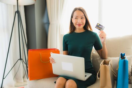 Portrait beautiful young asian women sitting on sofa chair using computer laptop or smart and mobile phone with credit card for online shopping Banco de Imagens - 135533258