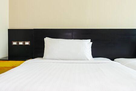 Kissen und Decke auf dem Bett mit Lichtlampendekoration des Schlafzimmers of Standard-Bild